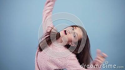 Потеха, довольно предназначенная для подростков девушка в ярком свитере, околпачивать, смотря камеру, надувает щеки, изолированны видеоматериал