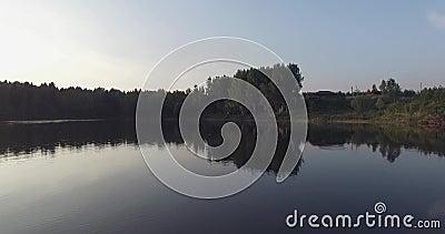 Полет над озером, ясность камеры любит зеркало Оно отражает деревья на береге, зеленой траве, деревянном доме и сини сток-видео