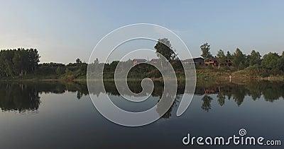 Полет над озером, ясность камеры любит зеркало Оно отражает деревья на береге, зеленой траве, деревянном доме и сини акции видеоматериалы