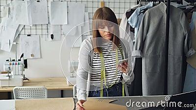 Предприниматель дизайна одежды проверяет проекты бумаги шить и смотрит smartphone Она рассматривает каждый вырез сток-видео