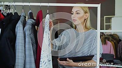 Предприниматель магазина одежды проверяющ и подсчитывающ одежды на рельсах пока работающ с таблеткой Она inputting сток-видео