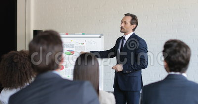 Представление успешного бизнесмена ведущее на встрече конференции, команде предпринимателей слушая на тренировочном семинаре сток-видео