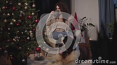 Прекрасная кавказская женщина сидит на кресле, пьет чай или кофе и ест печенье Её прелестное животное лежало у акции видеоматериалы