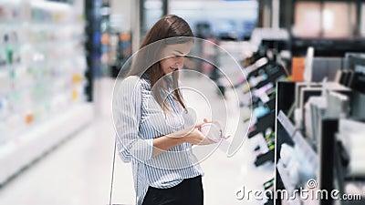 Прекрасная молодая женщина выбирает косметический мешок в магазине косметики акции видеоматериалы