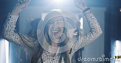 Прекрасная молодая счастливая кавказская женщина бьет по конфетти, делая желание на магическом праздновании дня рождения медленно видеоматериал
