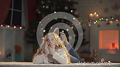 Прелестное письмо сочинительства девушки под накаляя рождественской елкой мечтая о чуде сток-видео