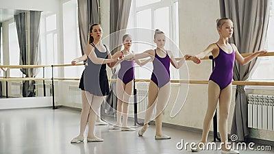 Прелестные маленькие девочки в ярких bodysuits имеют урок классического балета уча движения ноги с учителем в искусстве видеоматериал