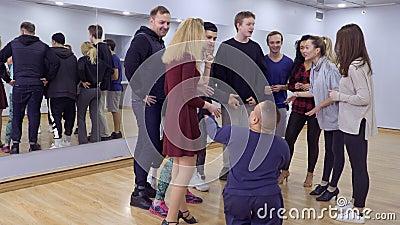Приветствия группы людей их маленький друг в студии сток-видео