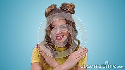 Привлекательная маленькая девочка в желтой рубашке показывает жест запрета и усмехаться пока смотрящ в камеру сток-видео