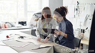 Привлекательные предприниматели дизайнера одежд конспектируют вырез с мелом, работающ с таблеткой и говорить Занятый день на акции видеоматериалы