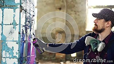 Привлекательный бородатый парень держит краску аэрозоля и рисуя граффити на штендере внутри просторного покинутого дома творческо видеоматериал