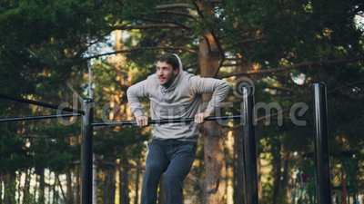 Привлекательный парень работает outdoors используя турник делая усилие улучшить мышцы и увеличить силу сток-видео
