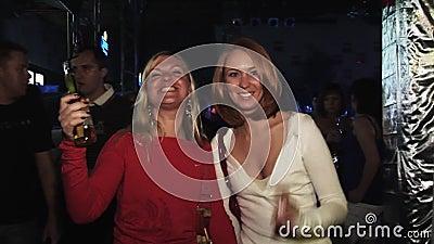 Привлекательные девушки представляют на камере на партии в ночном клубе Улыбка Бутылка пива в руках зрелищность акции видеоматериалы