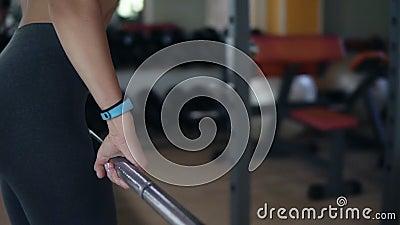 Пригонка, белокурая женщина бросает пустой бар над ее головой пока стоящ в фронте зеркало в фитнес-клубе подготовлять акции видеоматериалы