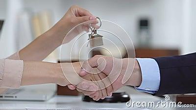 Продавец дает женщинам ключи от квартиры и пожимает руку, покупает имущество видеоматериал
