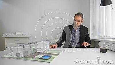 Проекты и печати бизнесмена футуристической недвижимостью кибер увеличенной и смешанной сток-видео