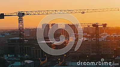 промышленно Строительная площадка в середине города Поднимать работу кранов Заход солнца Статическая съемка видеоматериал