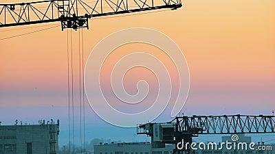промышленно Строительная площадка в середине города Поднимать работу кранов Румяный заход солнца видеоматериал