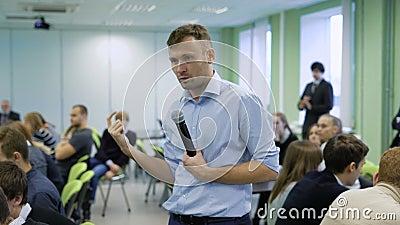 Профессиональный тренер в голубой рубашке говоря в микрофон и жестикулируя на мастерской для будущих менеджеров высшего звена a видеоматериал
