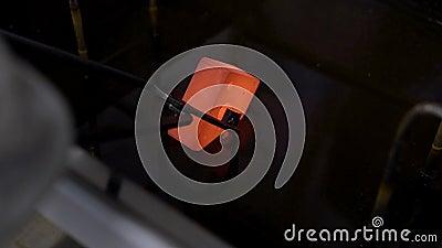 Работник держит нагретую деталь металла щипчиками и inputting он в холодной воде для охлаждать, конец-вверх сток-видео