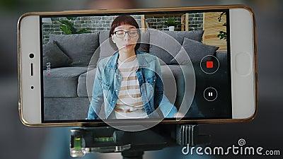 радостная девушка записывает видео с помощью смартфона, показывая жесты дома акции видеоматериалы