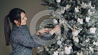 Радостная молодая женщина украшает дерево Нового Года со стильными серебряными шариками и золотыми светами наслаждаясь празднично сток-видео