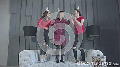 Радостные женщины в шляпах партии скача на кресло сток-видео