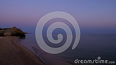 Рассвет Морские волны омывают песчаный пляж скалистый скал протекает в море Небо меняет цвет акции видеоматериалы