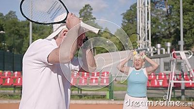 Расстроенные зрелые пары потеряли турнир на теннисном корте Старший человек и женщина держа голову с руками сток-видео