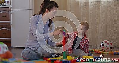 Ребенк и мать строя большую башню играя игры movKid и мать строя большую башню играя игры и начиная точный двигательный навык сток-видео