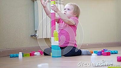 Ребенок играет с конструктором Развитие ребенка Счастливая девочка строит башню из конструктора сток-видео