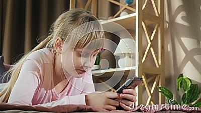 Ребенок отдыхает в своей комнате, пользуется смартфоном сток-видео