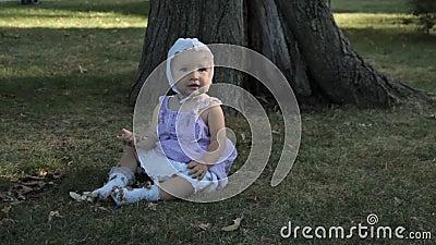 Ребёнок в bonnet сидя на траве и держа ручку акции видеоматериалы
