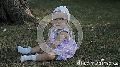 Ребёнок в bonnet сидя на траве и разрывах оно акции видеоматериалы