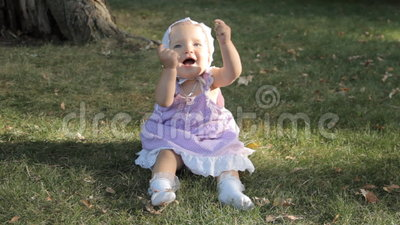Ребёнок в bonnet сидя на траве и хлопая ее руки акции видеоматериалы