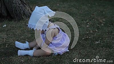 Ребёнок в bonnet сидя на траве акции видеоматериалы
