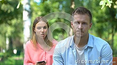 Ревная женщина ссорится с парнем, читает частные сообщения на его телефоне сток-видео