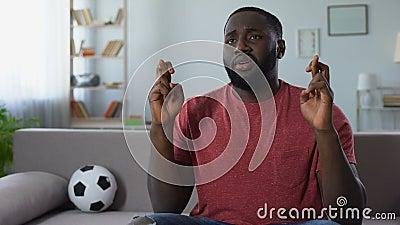Резвит пальцы скрещивания сторонника смотря игру на ТВ, веселя национальную команду акции видеоматериалы