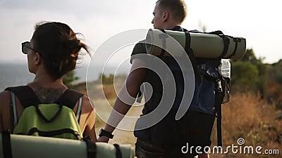 Рискуйте, путешествуйте, туризм, поход и концепция людей Редкий отснятый видеоматериал пары hiling холмы вместе с рюкзаками сток-видео