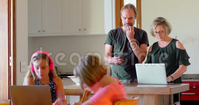 Родители используя компьтер-книжку и мобильный телефон пока дети изучая в кухне 4k акции видеоматериалы