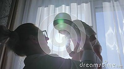 Родительство, темная диаграмма матери поднимает в руки newborn поднимающее вверх дома против окна на выходных акции видеоматериалы