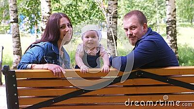 Родная мама девочка и папа сидят на скамейке в парке, смотря на камеру улыбаясь сток-видео