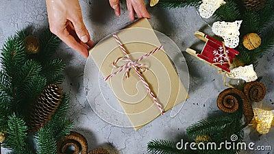 Рождественские украшения, праздничный декор, сосновая ветвь, сосновый конус, ягоды Женские руки передвигают подарок к искусственн акции видеоматериалы