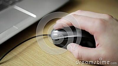 Рука молодого кавказского человека щелкая и перечисляя мышь видеоматериал