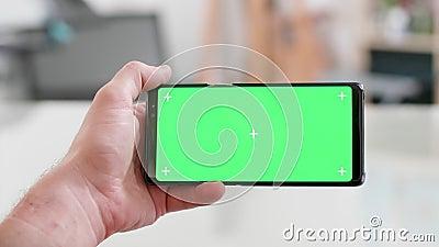 Рука человека держа смартфон горизонтально с зеленым экраном дальше сток-видео