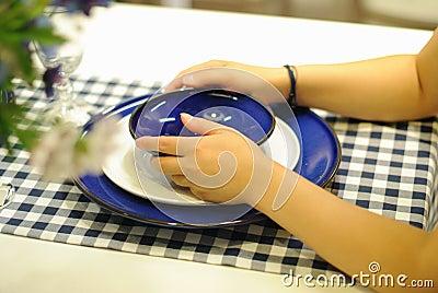 Рука девушки держа плиты на таблице