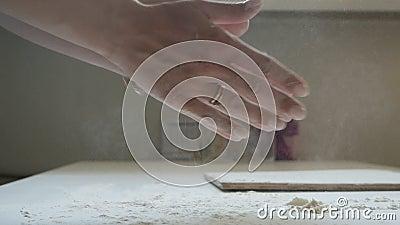 Руки девушки хлопают мукой на столе домашняя кухня акции видеоматериалы