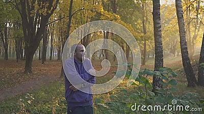 Руки красивого чувства человека холодные и грея, человек замерзают в парке осени холодно видеоматериал