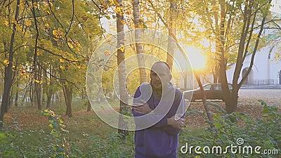 Руки красивого чувства человека холодные и грея, человек замерзают в парке осени холодно сток-видео