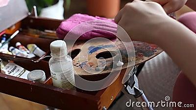 Руки раскрывают трубку краски и краски выжимкы на палитру Палитра художника с краской и щетками масла сток-видео